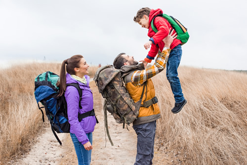 family hiking father lifting boy